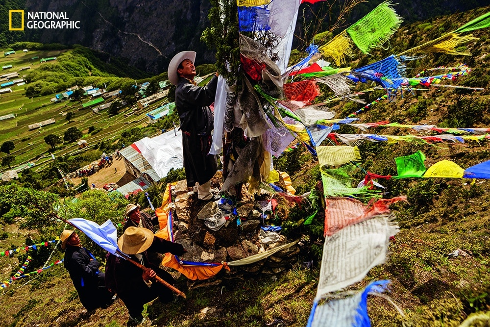 Photo by Aaron Huey/National Geographic Elders attach prayer flags outside Phortse at an altar for Khumbila, the god of the Khumbu.